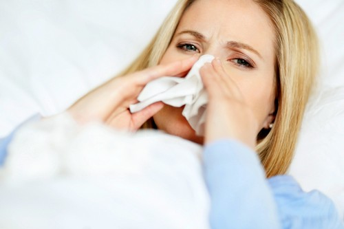 Closeup of a young woman having cold on bed